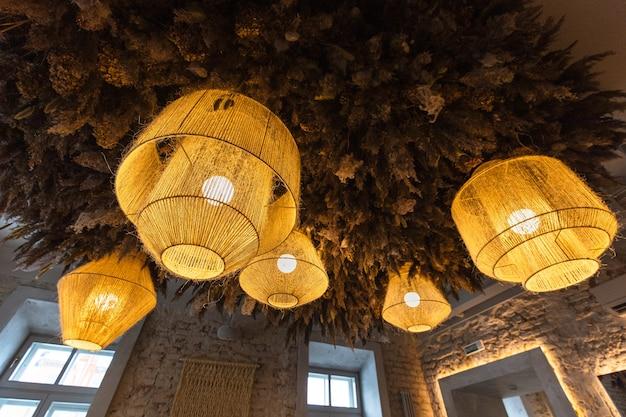 Роскошные горящие люстры различной формы в ресторане желтого цвета с растениями на потолке