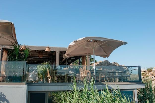 야자수와 바다가 내려다보이는 유리 발코니가 있는 고급스러운 카페