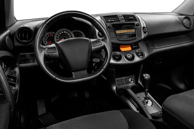 Luxurious car interior - steering wheel, shift lever and dashboard on white isolated background