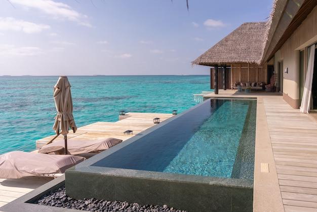 천연 목재로 장식 된 몰디브에있는 매우 값 비싼 고급 워터 빌라의 고급스러운 외관.