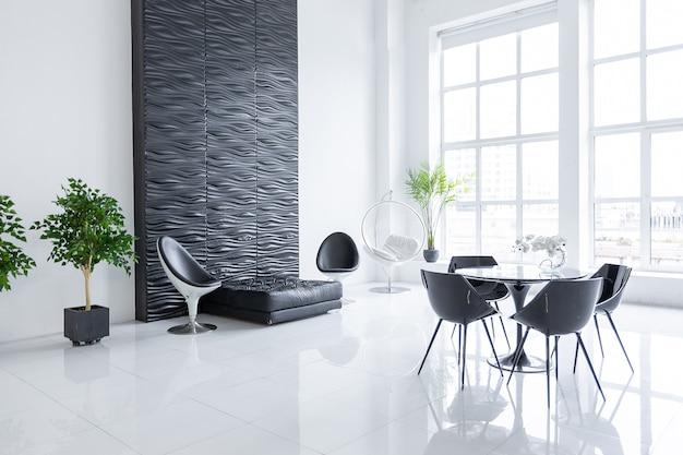 Роскошный футуристический модный современный интерьер в контрастных черных и белых тонах с интересной модной черной мебелью и декорированной стеной.