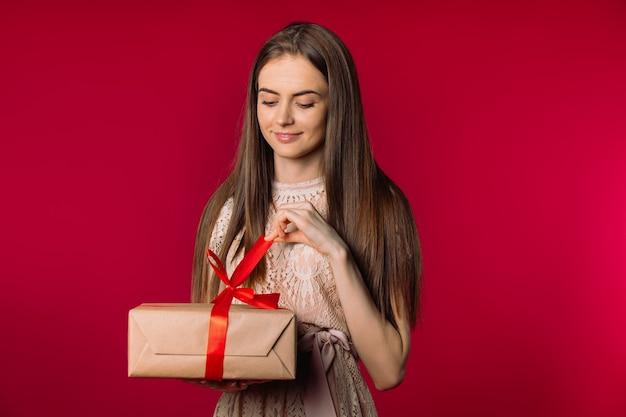 빨간색 배경 휴일 개념에 선물 상자 사진을 여는 고급스러운 소녀