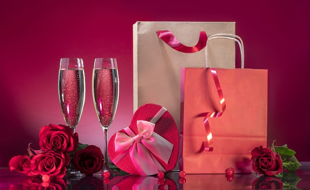 Luxurious glasses with sparkling wine and gift box in the shape of a heart with satin