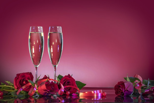 Luxurious glasses with sparkling wine and gift boxes in the shape of a heart with satin bows