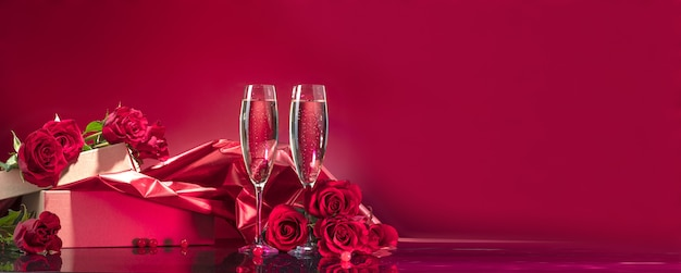 Luxurious glasses with sparkling wine open box with glitter brocade surrounded