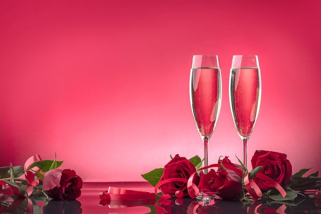 Luxurious glasses with sparkling wine surrounded by roses on a mirror surface
