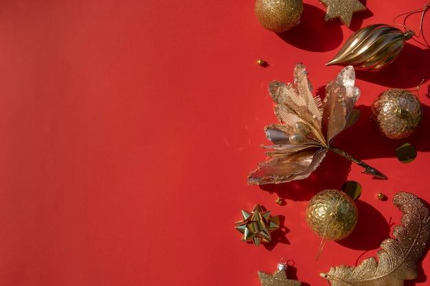 コピースペースのある赤い背景にさまざまな装飾品の豪華なゴールドのクリスマスフラットレイ