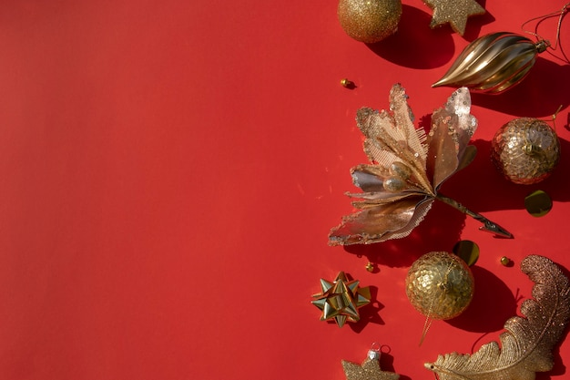 Luxurious gold christmas flat lay of various ornaments on a red background with copy space