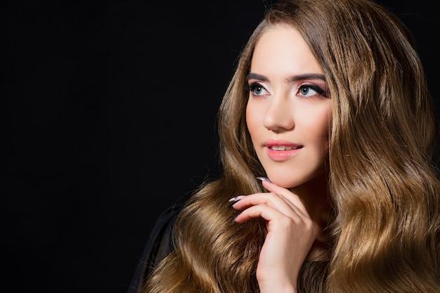 Роскошные золотые кудри, портрет молодой красивой женщины с красивыми волосами, черный фон копией пространства слева