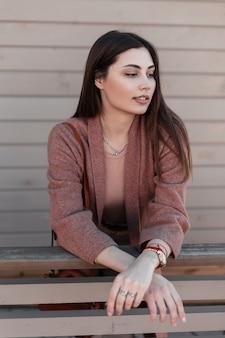 세련된 봄 코트에 긴 머리를 가진 고급스러운 화려한 젊은 여성 패션 모델은 거리에 나무 난간 근처에 선다. 트렌디 한 캐주얼 겉옷에 아름다운 세련된 소녀가 야외 휴식을 즐깁니다.