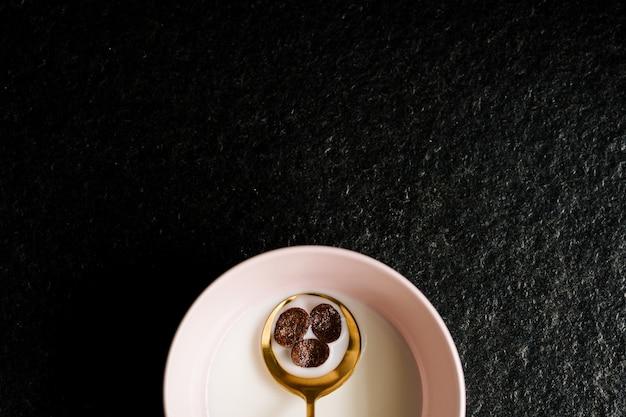 고립 된 우유의 전체 분홍색 그릇에 시리얼과 고급스러운 녹색과 황금 숟가락