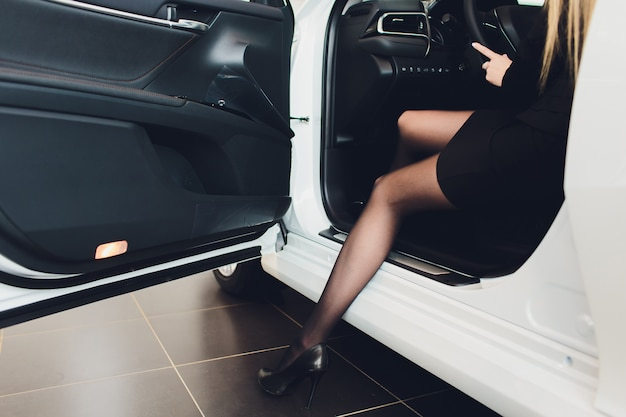 Luxurious lady sitting with the door open in the white car.