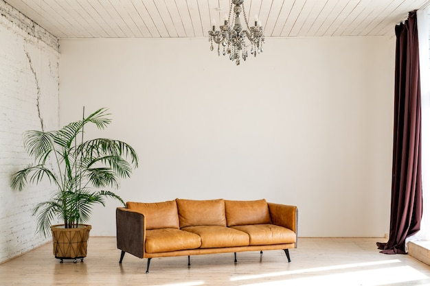 A luxurious large bright living room with a large green potted plant in an industrial style with a brown leather sofa and a brick-and-white wall.