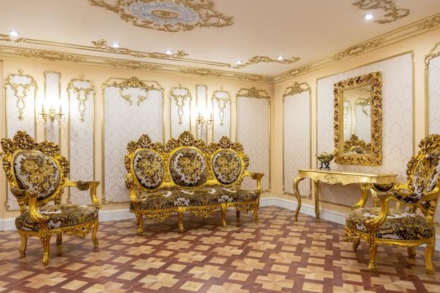 왕궁 스타일의 벽에 장식 된 금색의 아름다운 오래된 조각 가구가있는 고급스러운 거실 인테리어