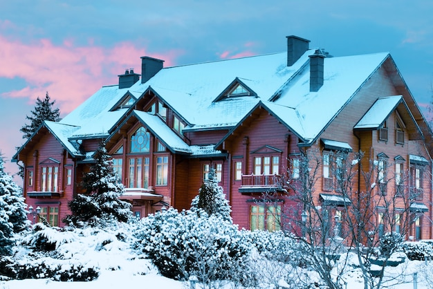 Роскошный бревенчатый дом, деревянный особняк, покрытый снегом в зимнем парке во время заката.