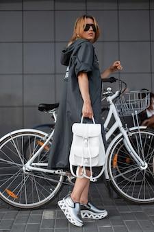 배낭과 세련된 운동화 선글라스에 세련된 긴 재킷에 고급스러운 모델 예쁜 젊은 여자는 자전거 주차장 근처 야외에서 포즈. 도시 소녀는 도시를 안내합니다.