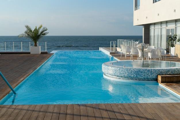 海沿いにあるスイミングプール付きの豪華でモダンなヴィラ。成功したライフスタイルの豊かな休暇の概念