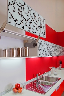Luxurious new red kitchen with modern appliances with red decoration Premium Photo
