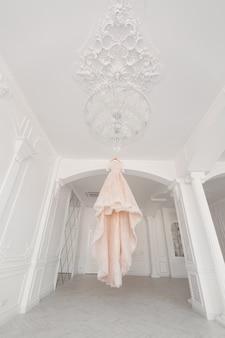 白い部屋でシャンデリアの豪華な桃のウェディングドレス