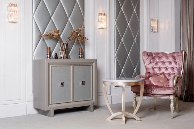 豪華なピンクのベルベットのアームチェアとリビングルームのアンティークの彫刻が施された家具