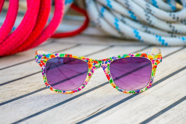 Luxurious purple glasses lie on the deck of the yacht while traveling.