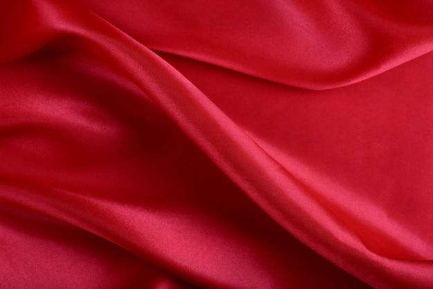 Роскошная красная атласная ткань с красивыми узорами.