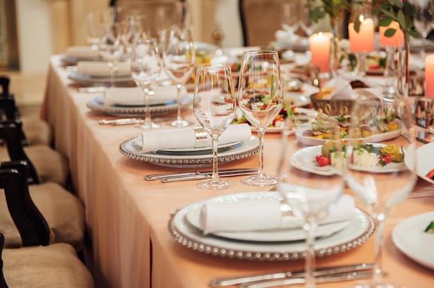 고급스러운 레스토랑. 고급스러운 인테리어, 흰색 테이블, 손님을위한 접시와 잔을 제공합니다.