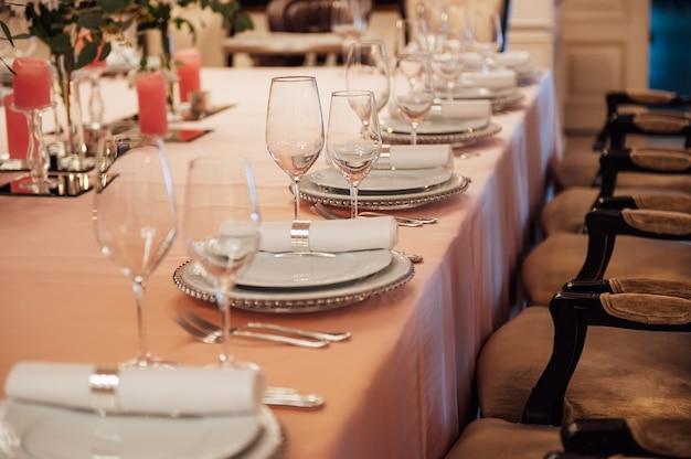 Роскошный ресторан. роскошный интерьер, белые столы, сервировочная посуда и бокалы для гостей.
