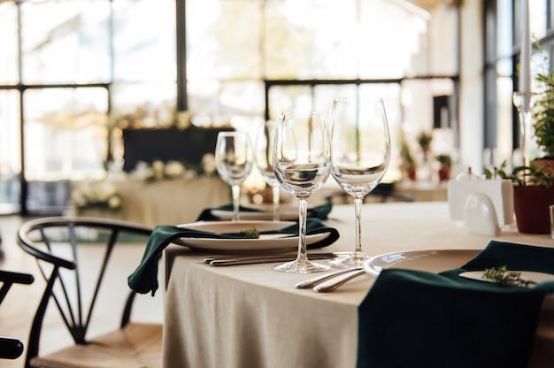 豪華なレストラン豪華なインテリアの白いテーブルでゲストに料理とグラスを提供