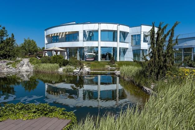 화창한 여름날 뒤뜰에 있는 작은 인공 연못의 물에 반사된 둥근 모양과 넓은 창문이 있는 고급스럽고 세련된 흰색 2층 컨트리 하우스