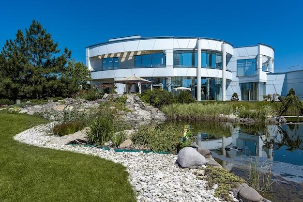 Роскошный стильный белый двухэтажный загородный дом с широкими окнами и ухоженным двором с небольшим искусственным прудом, украшенным декоративными растениями, галькой и садовой скульптурой летом.