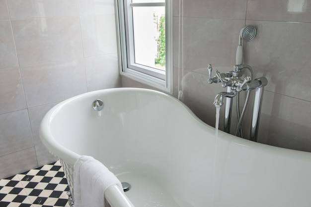 Luxurious tub in a modern bathroom, side windows view, bright sunlight, sunny day