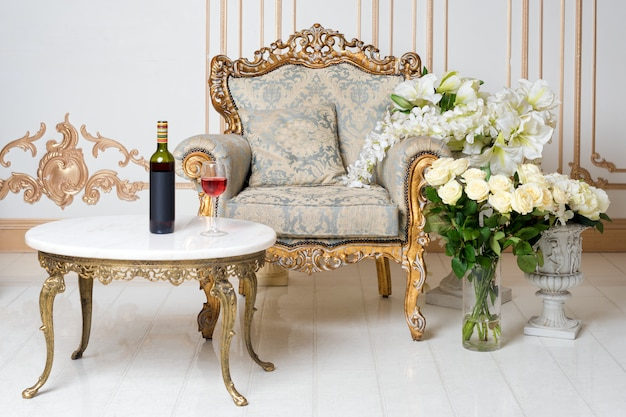 우아한 안락 의자와 꽃과 귀족 스타일의 고급스러운 빈티지 인테리어. 병 및 테이블에 와인 한잔입니다. 레트로 클래식.
