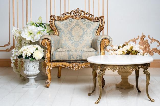우아한 안락 의자와 꽃과 귀족 스타일의 고급스러운 빈티지 인테리어. 레트로 클래식.