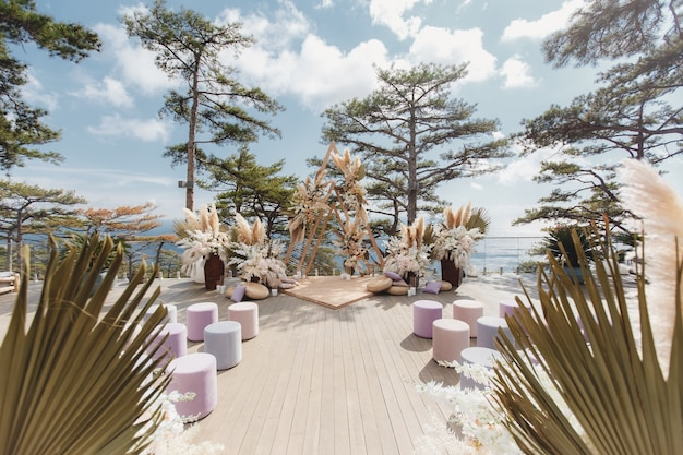 Luxurious wedding ceremony in boho style on the background of the forest and the ocean.