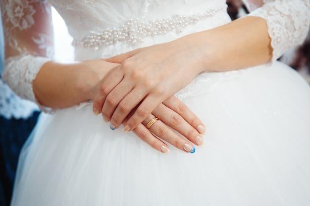 고급스러운 웨딩드레스. 최고의 결혼식 아침. 화이트 코르셋에 부드러운 드레스를 입은 신부를 정면에서 바라본 모습. 신부의 창조적 인 매니큐어