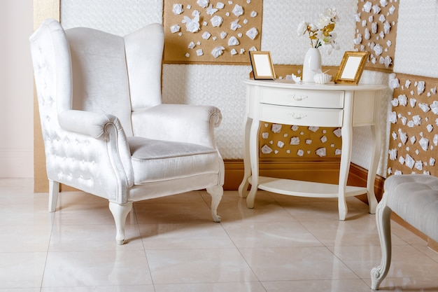 Luxurious white armchair and antique carved furniture on the living room