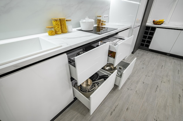 Luxurious white and black modern kitchen interior drawers pulled out