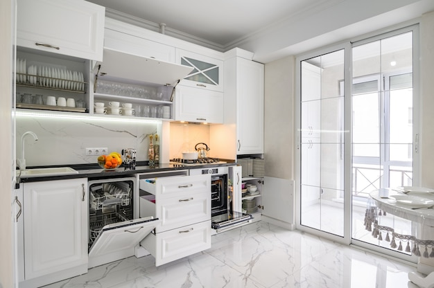 Luxurious white modern kitchen interior drawers pulled out dishwashers door open