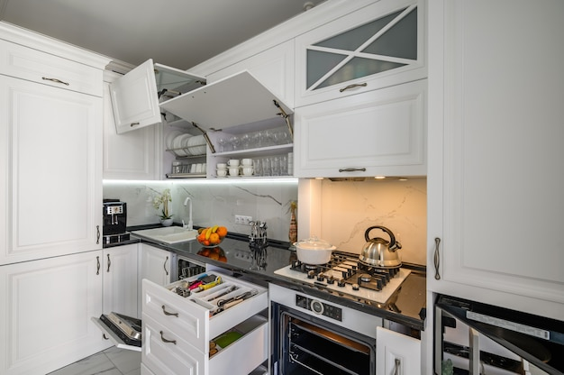 Luxurious white modern kitchen interior drawers pulled out doors open