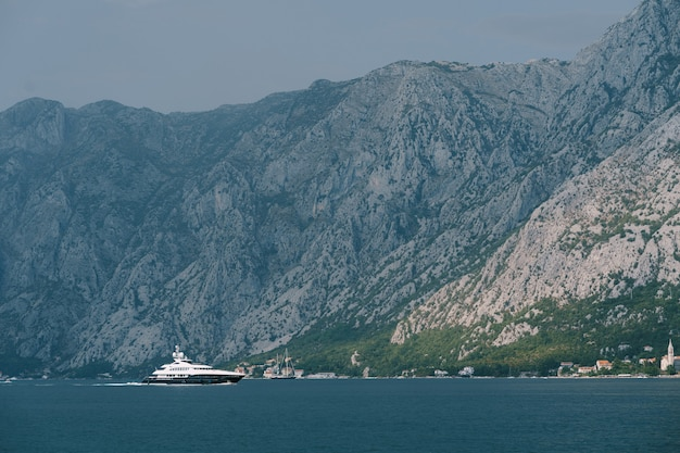 산이있는 코 토르만을 따라 항해하는 고급스러운 흰색 모터 요트