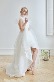 Luxurious white wedding dress on the girl's body. new collection of wedding dresses. morning bride, a woman waiting for the groom before the wedding ceremony. young bride in a long dress