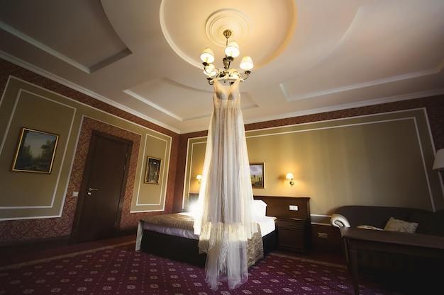 豪華な白いウェディングドレスがハンガーに掛かっています。