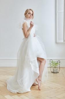 女の子の体に豪華な白いウェディングドレス。ウェディングドレスの新しいコレクション。朝の花嫁、結婚式の前に新郎を待っている女性。ロングドレスの若い花嫁