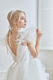 女の子の体に豪華な白いウェディングドレス。ウェディングドレスの新しいコレクション。朝の花嫁、結婚式の前に新郎を待っている女性