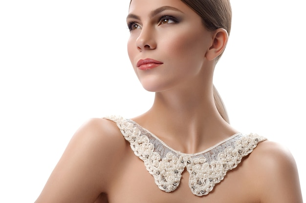 豪華な女性。スモーキーな目と白いスタイルの美しさのファッションアイコンの流行の概念で分離されたコピースペースでレースの襟のネックレスでポーズをとる裸のリップグロスメイクの美しい若い女性