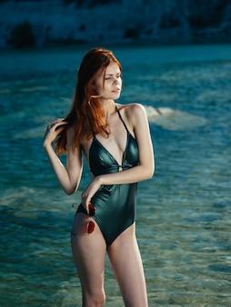 Роскошная женщина в зеленом купальнике с очками в руке у реки. фото высокого качества