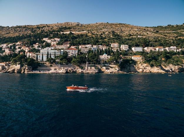 ドゥブロヴニクの旧市街近くの海岸を背景にモーター帆を備えた豪華な木製ボート