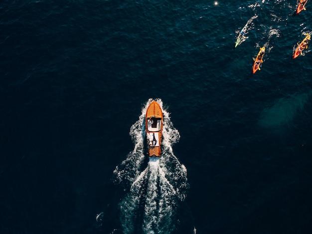 Роскошная деревянная моторная лодка несется по волнам адриатического моря. туристы плывут на байдарках с веслами.