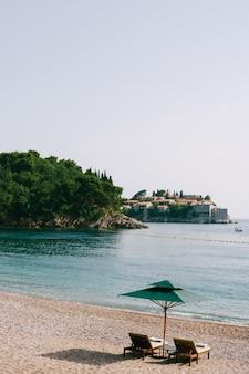 스베티(sveti) 근처 마일로세르 공원(milocer park)의 모래사장에 있는 고급스러운 나무 일광욕용 라운저와 녹색 해변 파라솔